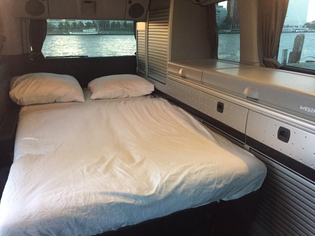 Opgemaakt bed beneden in camper